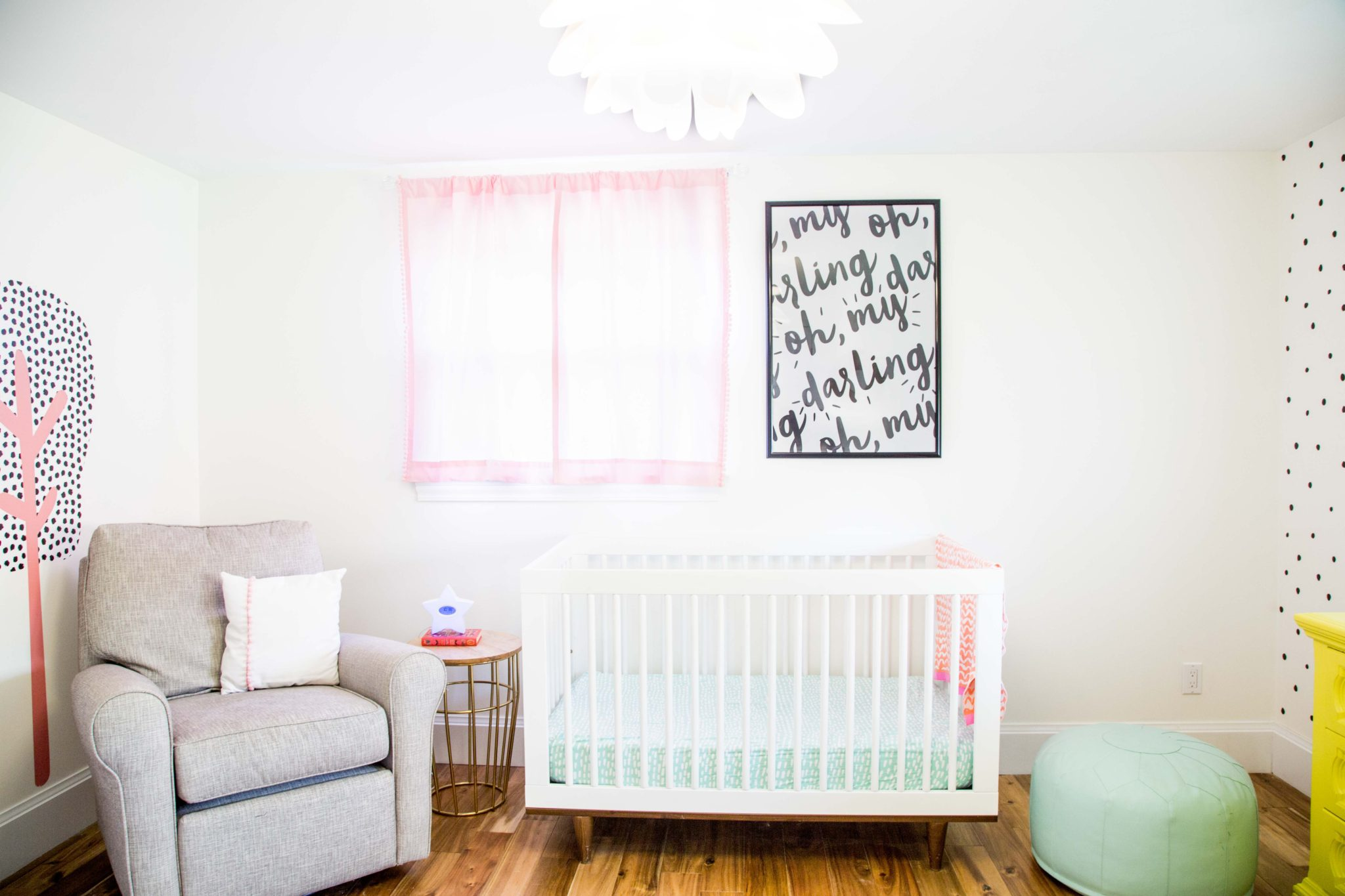 pretty and bright girls bedroom | bright nursery for baby girl | yellow dresser | the lovely wall co. decals | ikea picture ledge bookshelves | allweareblog.com